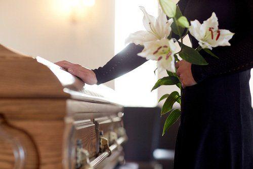 persona con fiori appoggiando la mano destra su una bara