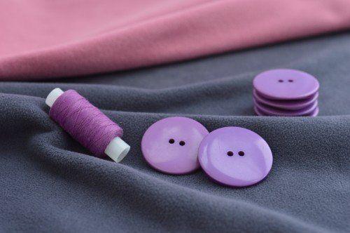 Bottoni e filo lilla sul tessuto grigio