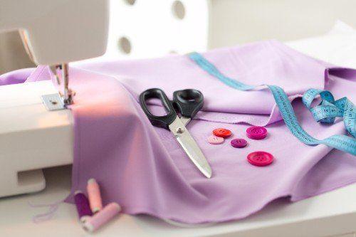 Vista di un tessuto rosa, di un metro,delle forbici, bottoni di vari colori e filati di diversi colori