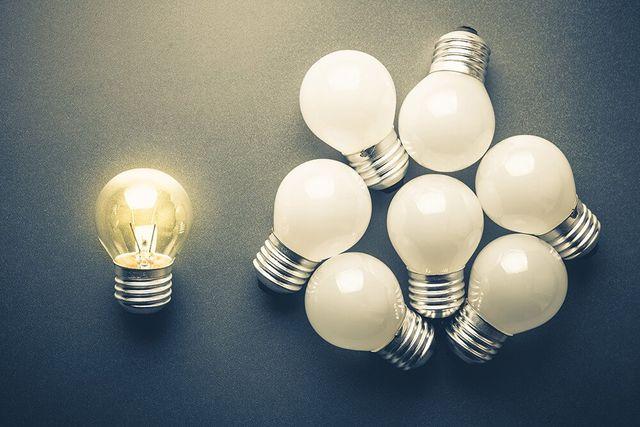 lit light bulb next to unlit light bulbs