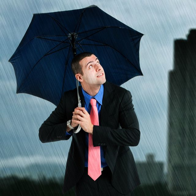 A business man in a suit holding an umbrella to protect him from the rain