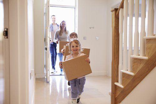 famiglia felice entra in casa con delle scatole di cartone