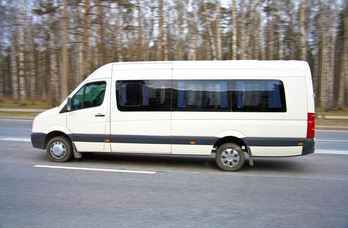 A white mini bus on the road