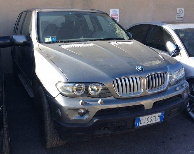 vista frontale di una vettura BMW di color grigio scuro parcheggiata