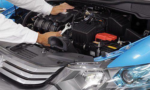 una vettura con il cofano aperto con vista del motore e un meccanico con una chiave inglese in mano