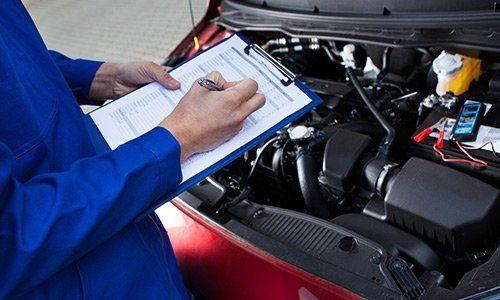 un meccanico con una tuta blu sta compilando una scheda tecnica di un veicolo messa sul rilievo di scrittura e di fronte c'è una vettura con il cofano aperto