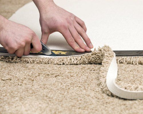 A carpet fitter cutting carpet