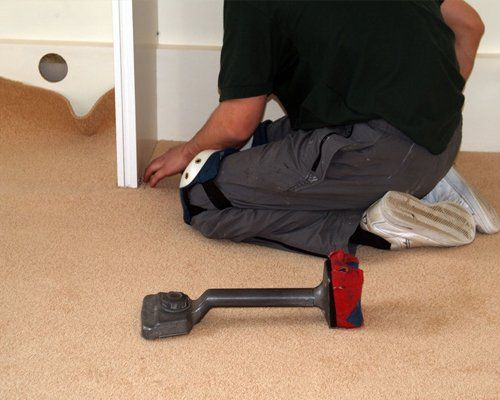 A carpet fitter at work