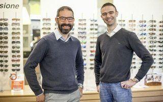 due persone dello staff davanti a un bancone sorridono alla fotocamera