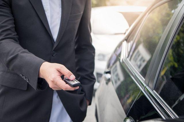 Un uomo in giacca che apre le sicure di un auto utilizzando il pulsante dell'antifurto centralizzato