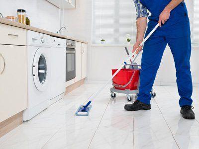 addetto lava il pavimento di una cucina