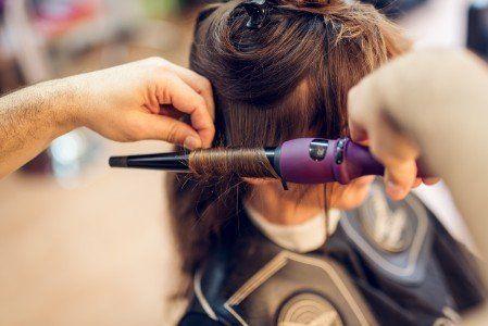 parrucchiere che fa dei capelli mossi