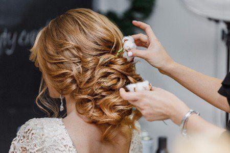 una parrucchiera mette dei fiori  nell'acconciatura della sposa