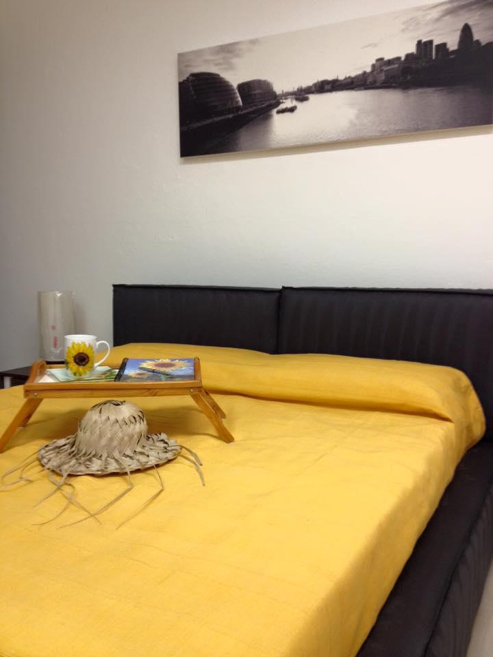 letto con coperte gialle e vassoio colazione