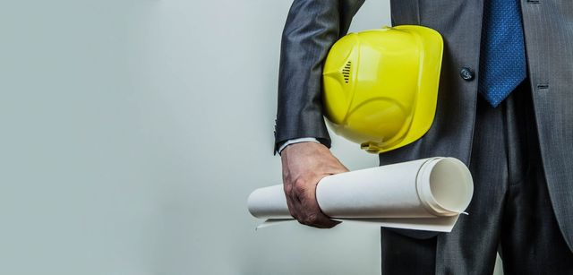 direzione lavori un uomo con un progetto e cappello giallo
