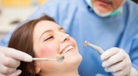 dentista durante una visita a una donna sorridente