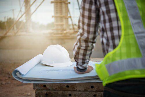 un ingegnere su un cantiere con una mappa davanti e un casco bianco poggiato su un banco