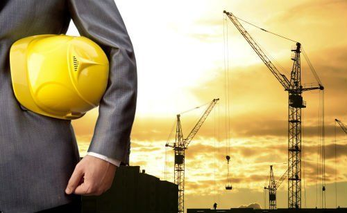 un uomo con un casco giallo da cantiere sotto braccio e delle gru sullo sfondo