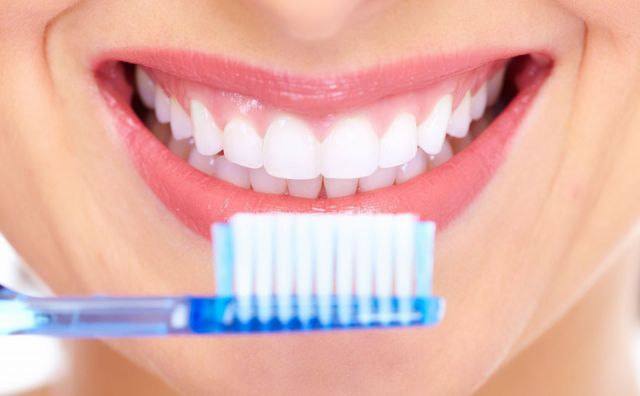 Woman brushing her teeth after seeing a dental specialist in Tauranga