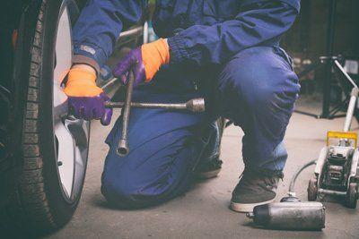 meccanico mentre regola le sospensioni di una ruota