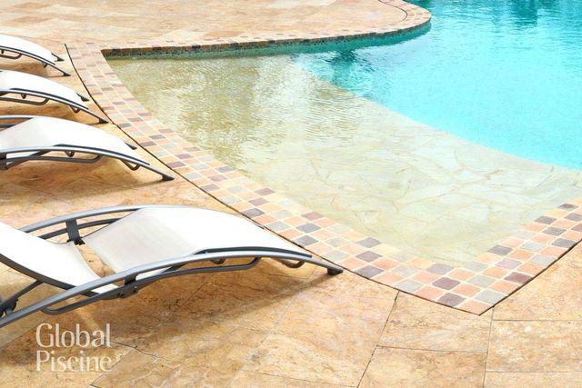 Una piscina con bordi a scacchi colorati e delle sdraio di fronte - logo Global Piscine