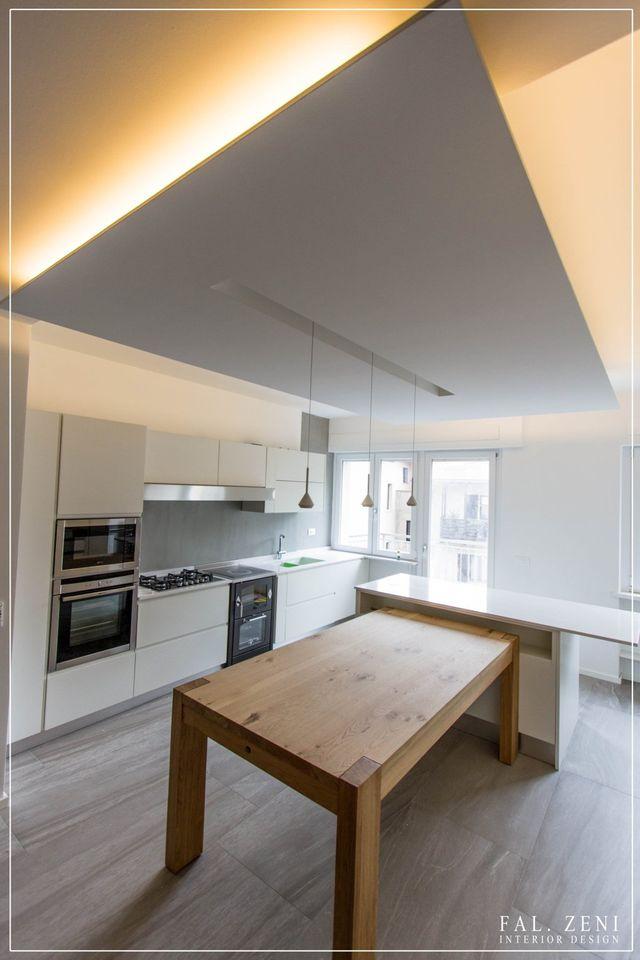 una cucina di una casa con mobili in legno, tavolo e soffitto in legno