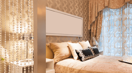 Bedroom decorated in beige and cream, with voile curtains at the large bedside window