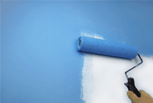 A white wall being painted blue with a paint roller