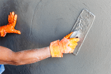 Orange-gloved hands plastering a white wall