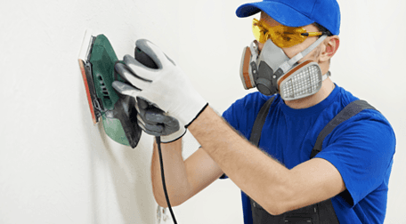 A plasterer at work wearing protective mask