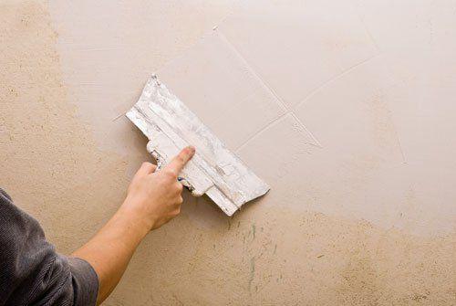 una mano con una spatola sul muro