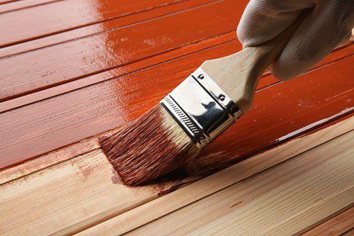 una mano con un pennello che sta verniciando del legno di bordeaux