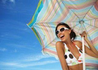Ragazza in bikini e con occhiali da sole sorridendo aguantando un ombrellone