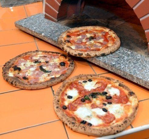 Pizze con mozzarella di bufala campana appena uscite dal forno a legna