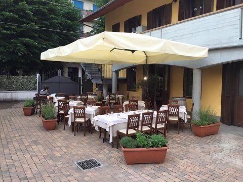 Tavoli apparecchiati sotto un ombrellone all'esterno del ristorante e pizzeria napoletana