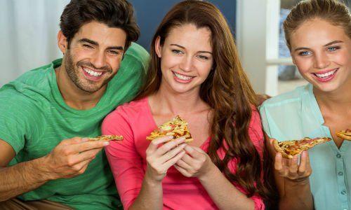 tre amici mangiano la pizza