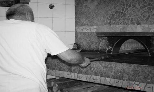 un pizzaiolo che inforna la pizza