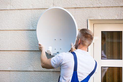addetto installa un'antenna satellitare