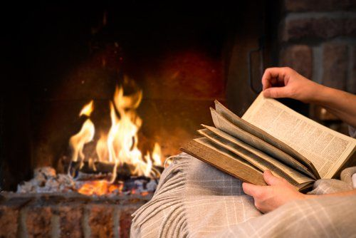Person reading a book by a cosy fireplace
