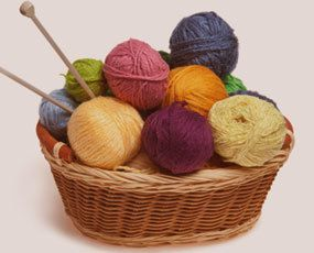 Two knitting needles and balls of coloured wool in a basket