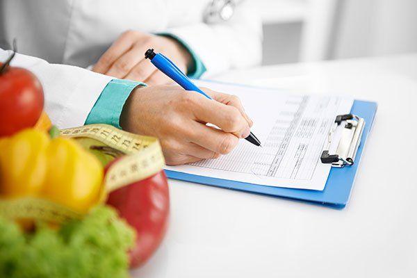 una mano di un dottore mentre scrive su un rilievo di scrittura