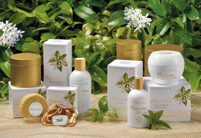 Confezioni di cosmetici Osmanthus della marca L'erbolario messi ad esposizione davanti a una pianta con dei fiori bianchi