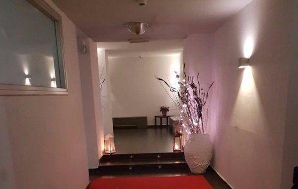 un  tappeto rosso due gradini e un vaso con dei rami