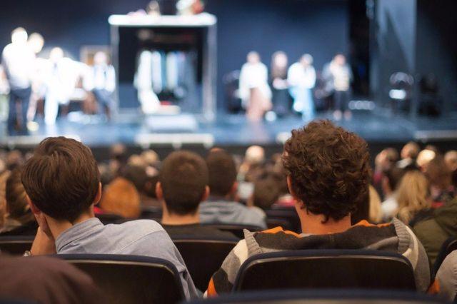 delle persone sedute durante uno spettacolo su un palco
