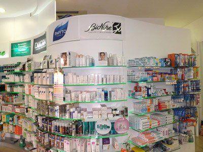 prodotti esposti all'interno della farmacia su delle mensole di vetro