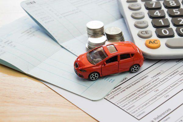 Alcuni documenti e sopra una calcolatrice, un auto giocattolo rosso  e varie monete