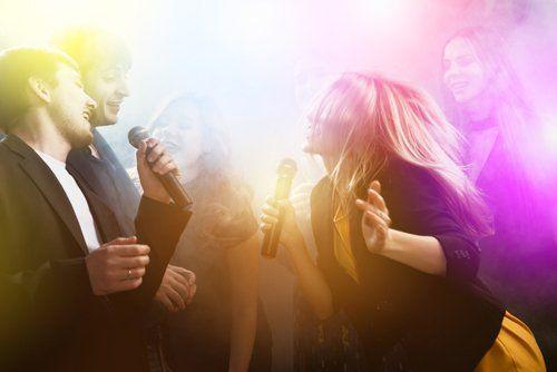 ragazzi e ragazze cantano al karaoke