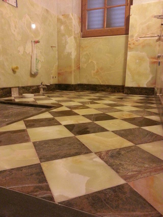 bagno con pavimento in marmo a scacchi e muro in marmo chiaro marmorizzato