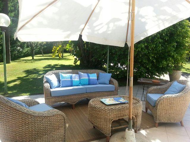 divanetti in paglia e bambù con cuscini azzuri e un ombrellone bianco