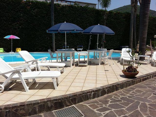 Bordo piscina con sdraio in plastica bianchi tavolini, sedie e ombrelloni bianchi e blu